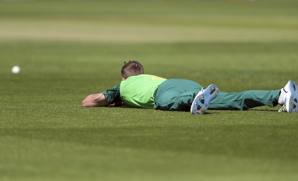 South Africa's bowler Chris Morris lies on the ground to avoid a swarm of bees that have come across the ground during the Cricket World Cup match bet...