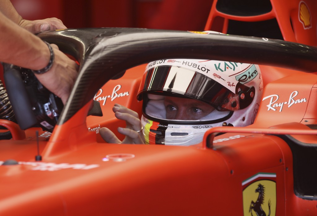 Ferrari driver Sebastian Vettel of Germany is handed the car's steering wheel in the team box during the first free practice session for the Austrian ...