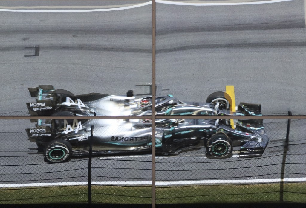 Mercedes driver Lewis Hamilton of Britain is reflected on windows steering his car during the first free practice session for the Austrian Formula One...