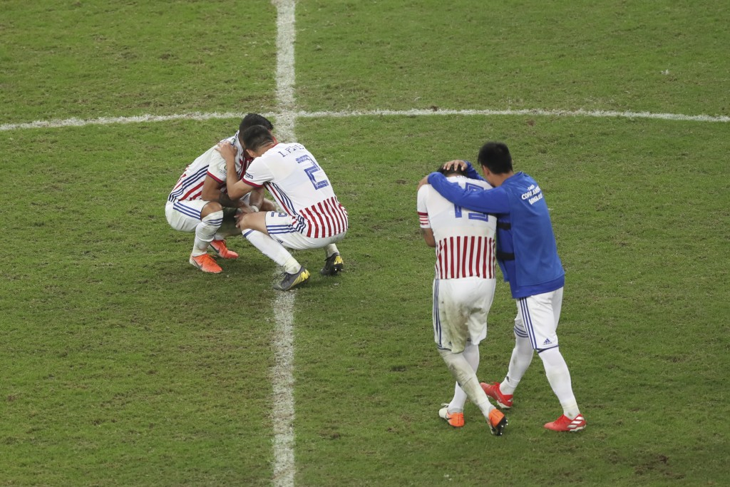 Paraguay's players embrace after their 3-4 los against Brazil in a penalty shoot-out in a Copa America quarterfinal soccer match at the Arena do Gremi...