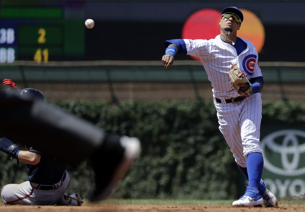 Chicago Cubs shortstop Javier Baez, right, throws out Atlanta Braves' Freddie Freeman at first after forcing out Dansby Swanson at second during the f...