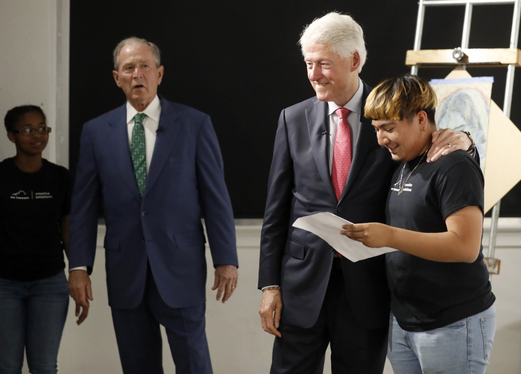Carletta, left, and former president George W. Bush, look on as former president Bill Clinton congratulates Sylvester, right, after her recited a perf...