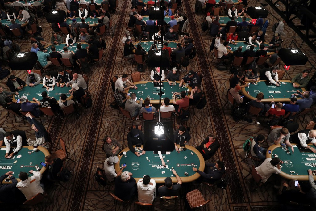 FILE - In this June 24, 2019, file photo, players and dealers sit at tables during a tournament at the World Series of Poker in Las Vegas.T ens of tho...