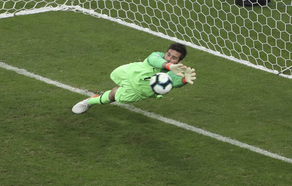 Brazil's goalkeeper Alison blocks the penalty kick by Paraguay's Gustavo Gomez during a Copa America quarterfinal soccer match at Arena do Gremio in P...