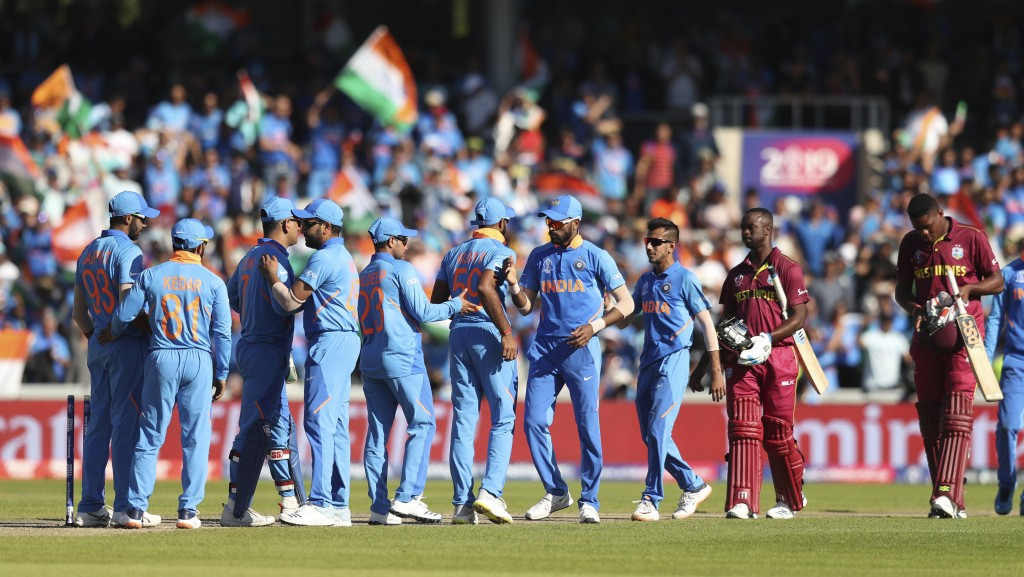 West Indies' cricketers walk past Indian cricketers celebrating their victory at the end of the Cricket World Cup match between India and West Indies ...
