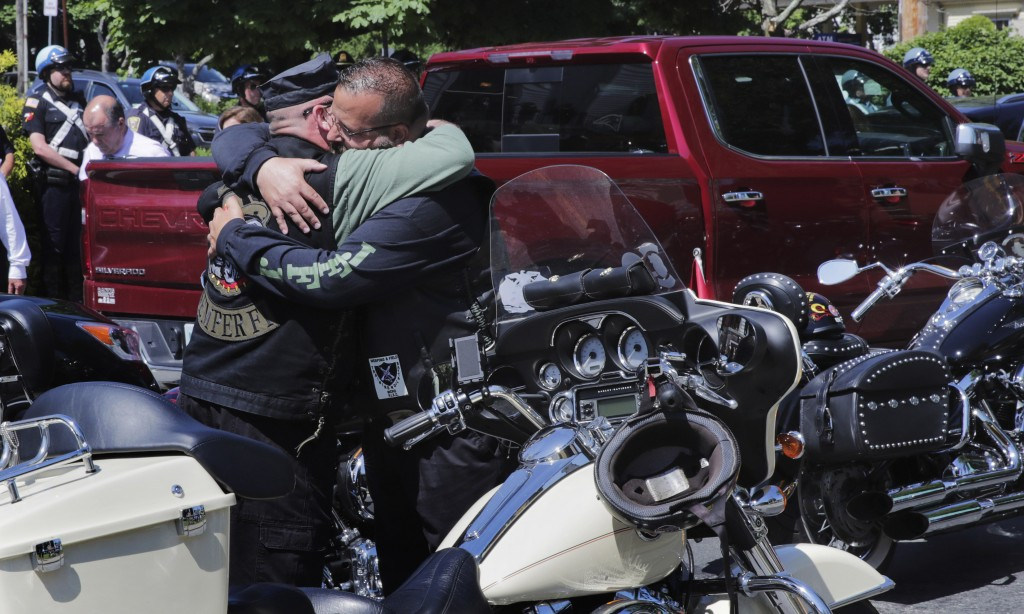 Members of the Jarheads Motorcycle Club embrace prior to the funeral for Michael Ferazzi at St. Peter's Catholic Church in Plymouth, Mass., Friday, Ju...