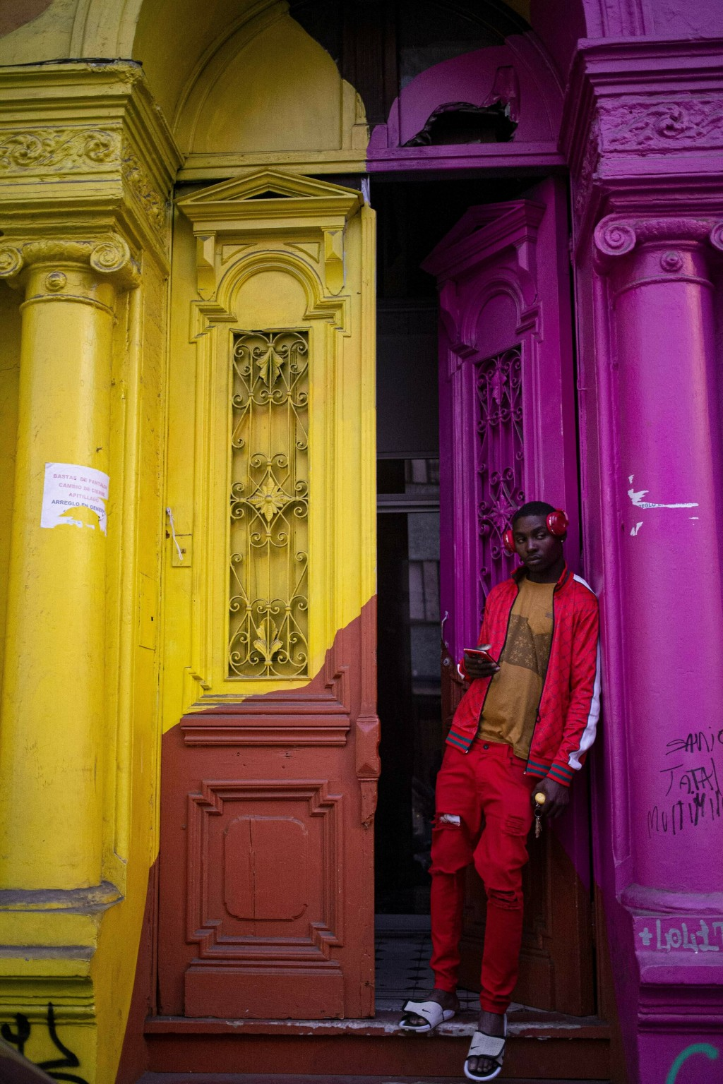A migrant listens to music while standing in the doorway of an home in downtown Santiago, Chile, Saturday, June 22, 2019. (AP Photo/Esteban Felix)