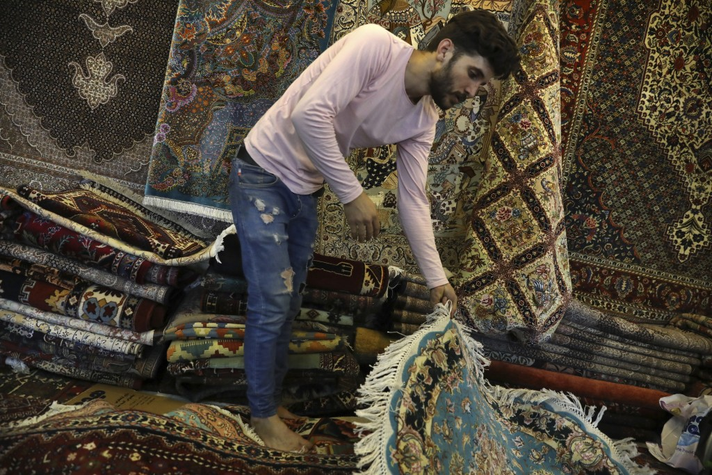 A carpet seller arranges hand-woven carpets at his stall at Jomeh Bazaar, or Friday Market, in Tehran, Iran, Friday, June 28, 2019. The Tehran's famou...