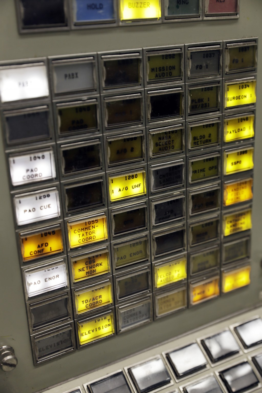 """Buttons are lit on a console for the Booster Systems Engineer, the first position on the first row known as """"The Trench,"""" inside the Apollo mission co..."""