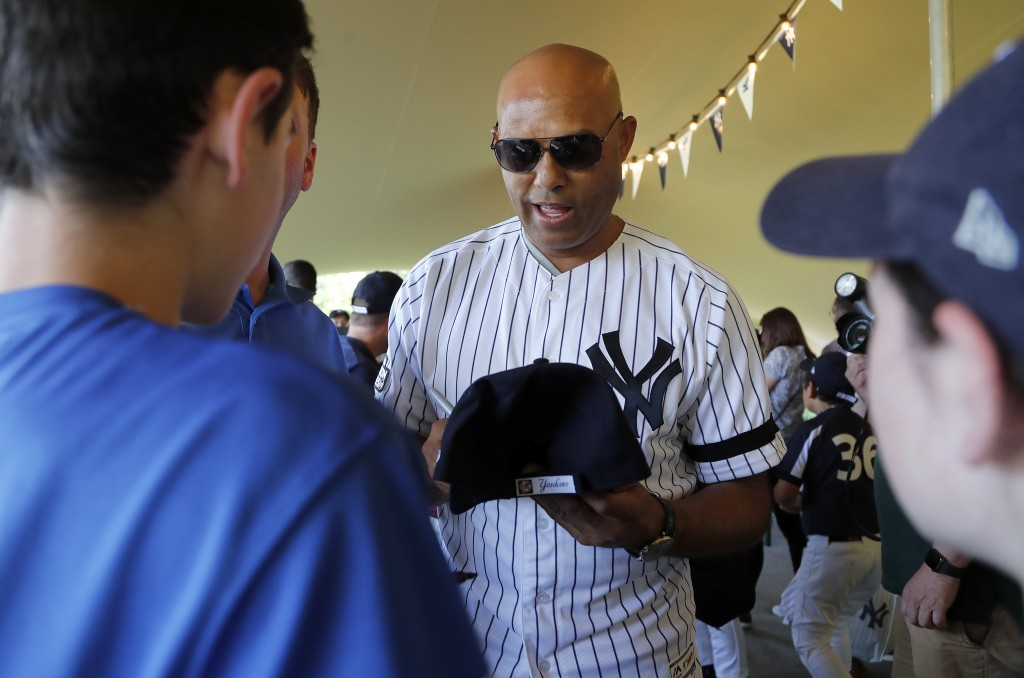 Yankees' Mariano Rivera signs baseball cap for young fans during a private Baseball Clinic in London, Thursday, June 27, 2019. The Yankees are hosting...