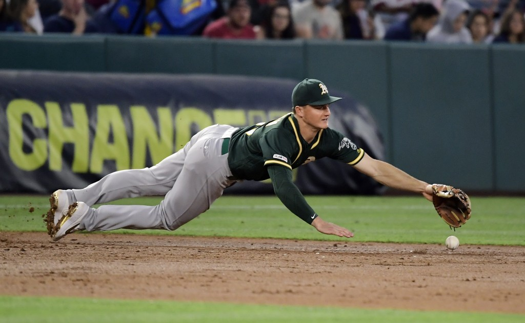 Oakland Athletics third baseman Matt Chapman can't reach a ball hit for single by Los Angeles Angels' Justin Upton during the third inning of a baseba...