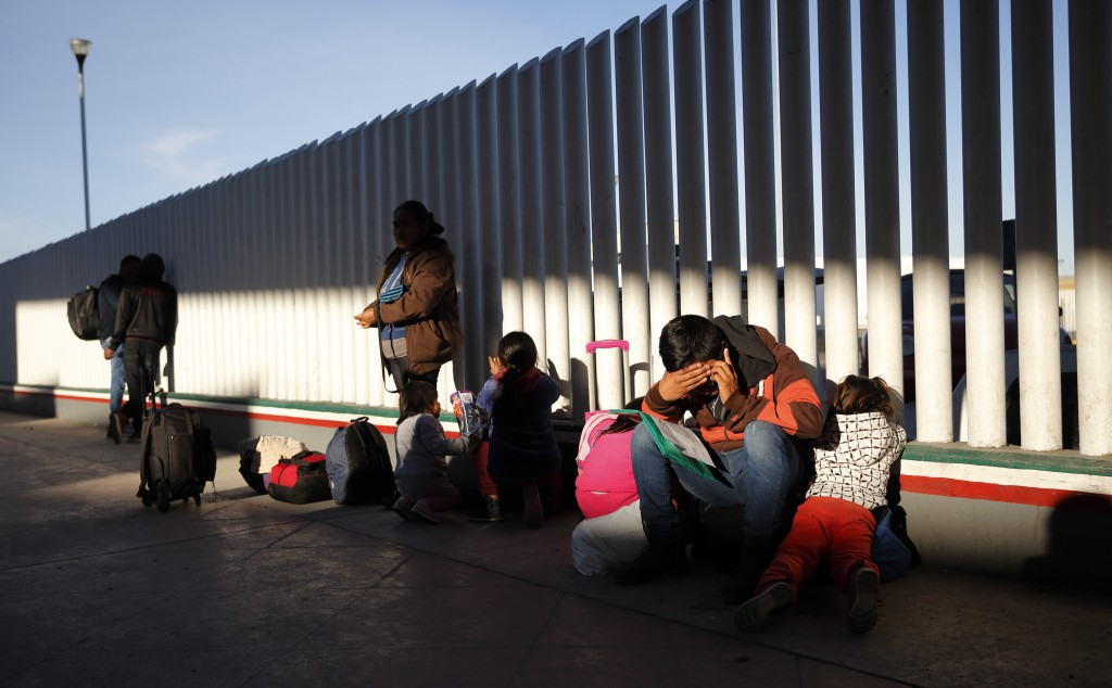 FILE - In this Jan. 25, 2019, file photo, a migrant sits with his children as they wait to hear if their number is called to apply for asylum in the U...