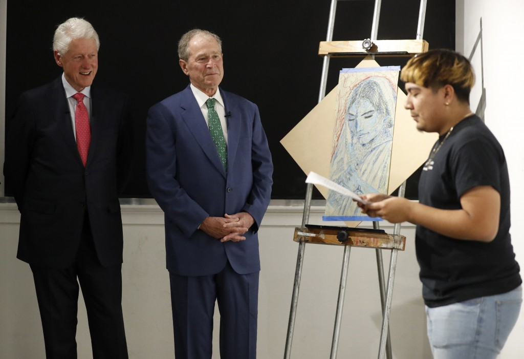 Former Presidents Bill Clinton, left, and George W. Bush, center, listen as Sylvester, right, recites a performance piece at the Meadows School of the...