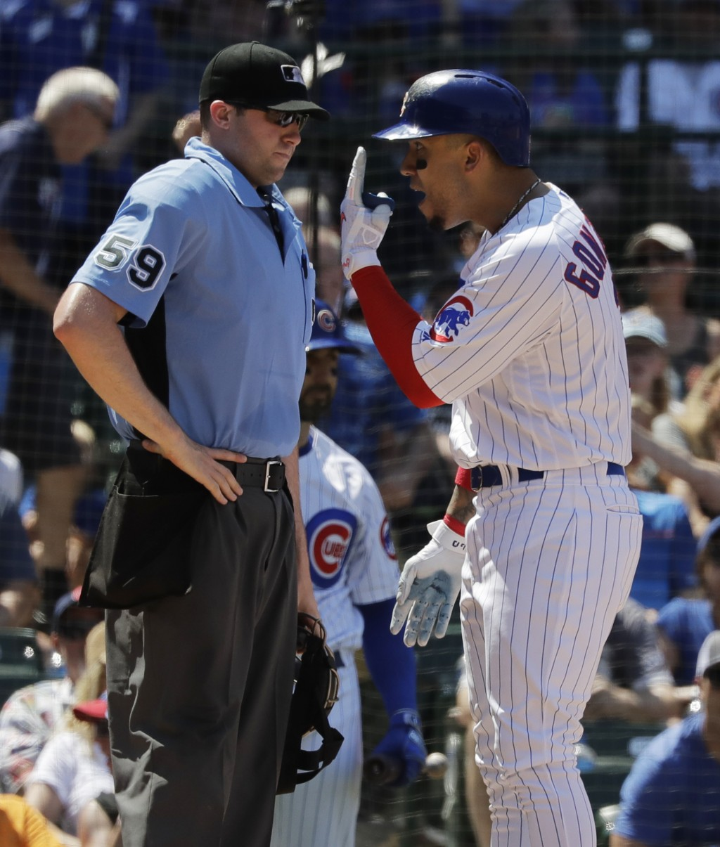 Chicago Cubs' Carlos Gonzalez, right, argues with home plate umpire Nic Lentz after being called out on strikes during the fourth inning of a baseball...