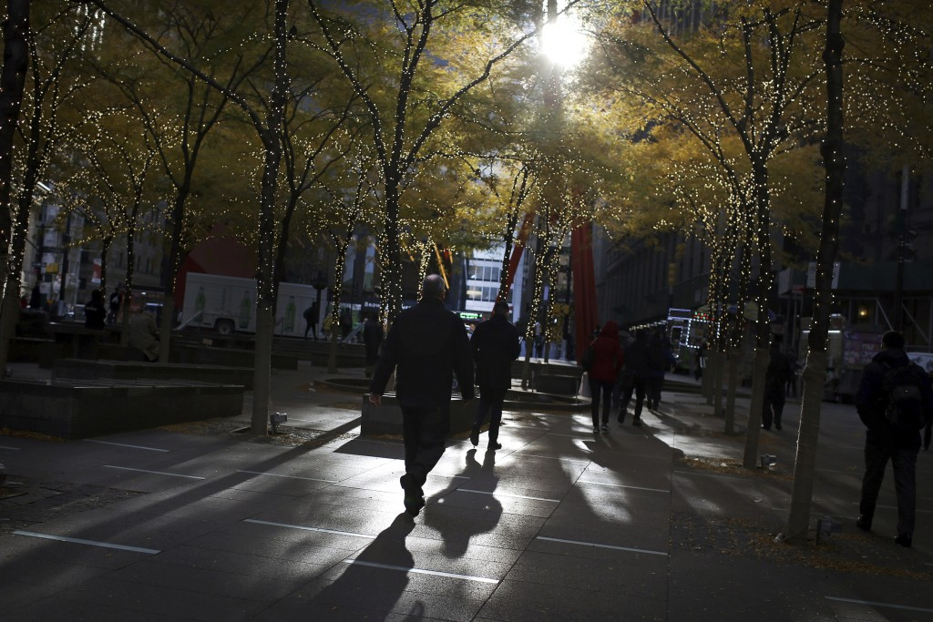 FILE - In this Nov. 14, 2018, file photo people walk through lower Manhattan's Zuccotti Park at the start of a work day in New York.A new study finds ...