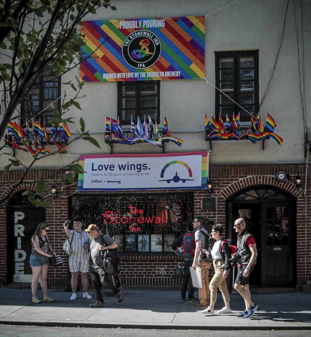 In this Monday, June 3, 2019 photo, visitors stop outside the Stonewall Inn in New York. Fifty years ago, the Stonewall Inn was an underground gay bar...