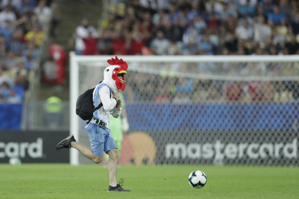 A soccer fan donning a rooster mask runs onto the pitch during a Copa America Group C soccer match between Chile and Uruguay at the Maracana stadium i...