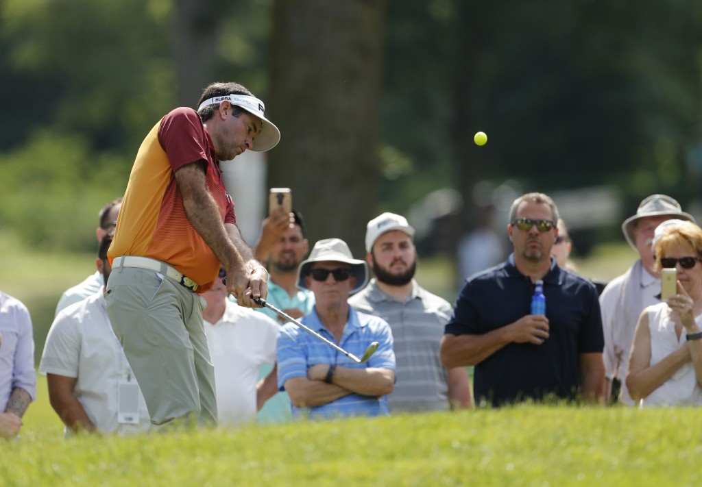 Bubba Watson hits his second shot from the gallery on the fourth hole during the first round of the Rocket Mortgage Classic golf tournament, Thursday,...