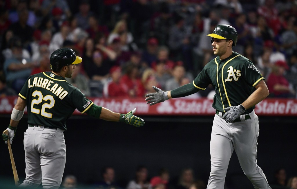 Oakland Athletics first baseman Matt Olson, right, is congratulated by Ramon Laureano after hitting a two-run home run during the fourth inning of the...