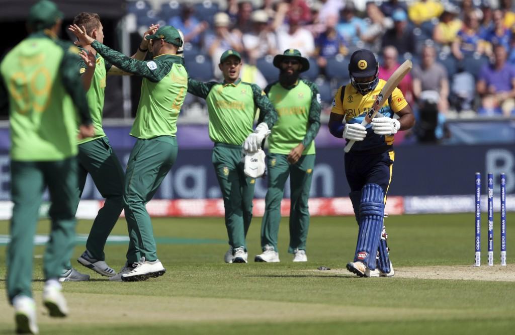 South Africa's bowler Dwaine Pretorius, far left, celebrates with teammates after bowling Sri Lanka's batsman Kusal Perera, far right, for 30 runs dur...