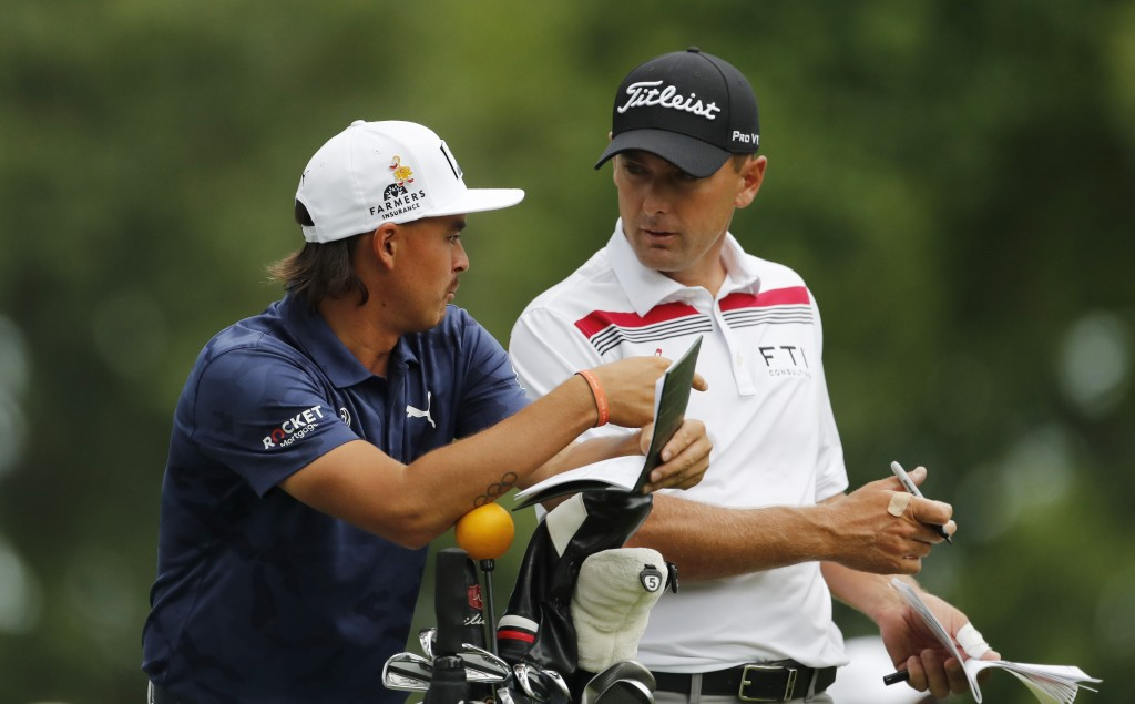 Rickie Fowler, left, and Charles Howell III talk on the ninth tee during the first round of the Rocket Mortgage Classic golf tournament, Thursday, Jun...