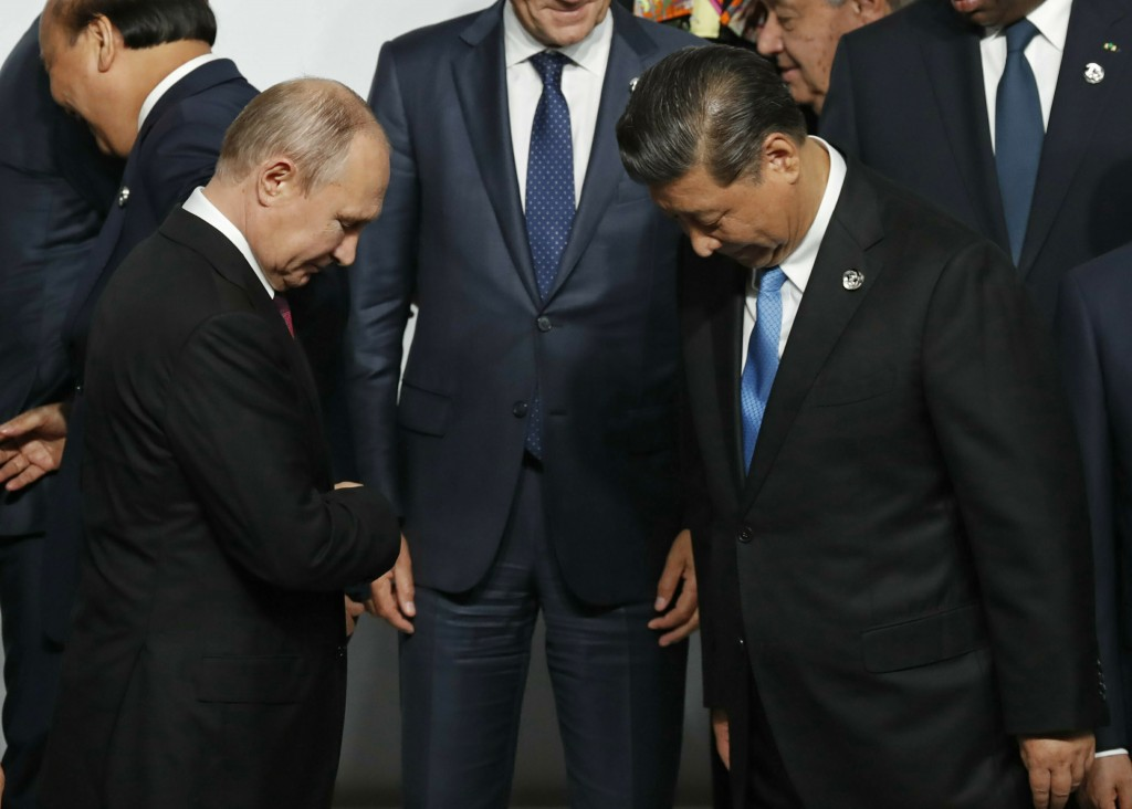 Russian President Vladimir Putin, left, and Chinese President Xi Jinping prepare for family photo session at G-20 leaders summit in Osaka, Japan, Frid...