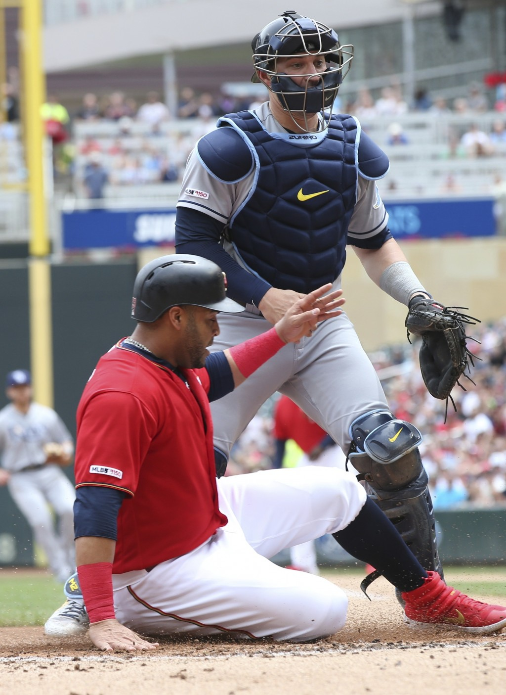 Minnesota Twins' Nelson Cruz, left, scores on a Luis Arraez single off Tampa Bay Rays pitcher Ryne Stanek as Rays catcher Mike Zunino, right, looks af...
