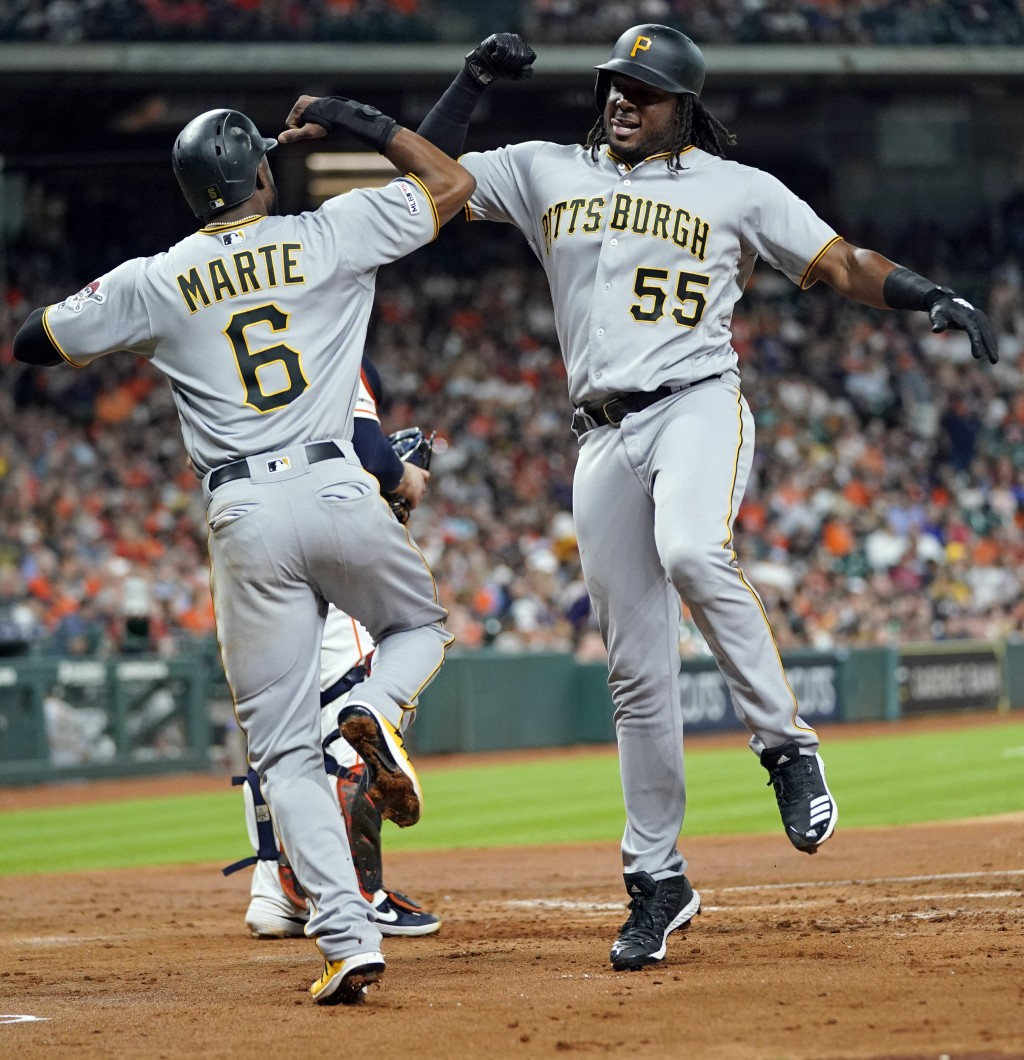 Pittsburgh Pirates' Josh Bell (55) celebrates with Starling Marte (6) after both scored on Bell's home run against the Houston Astros during the third...