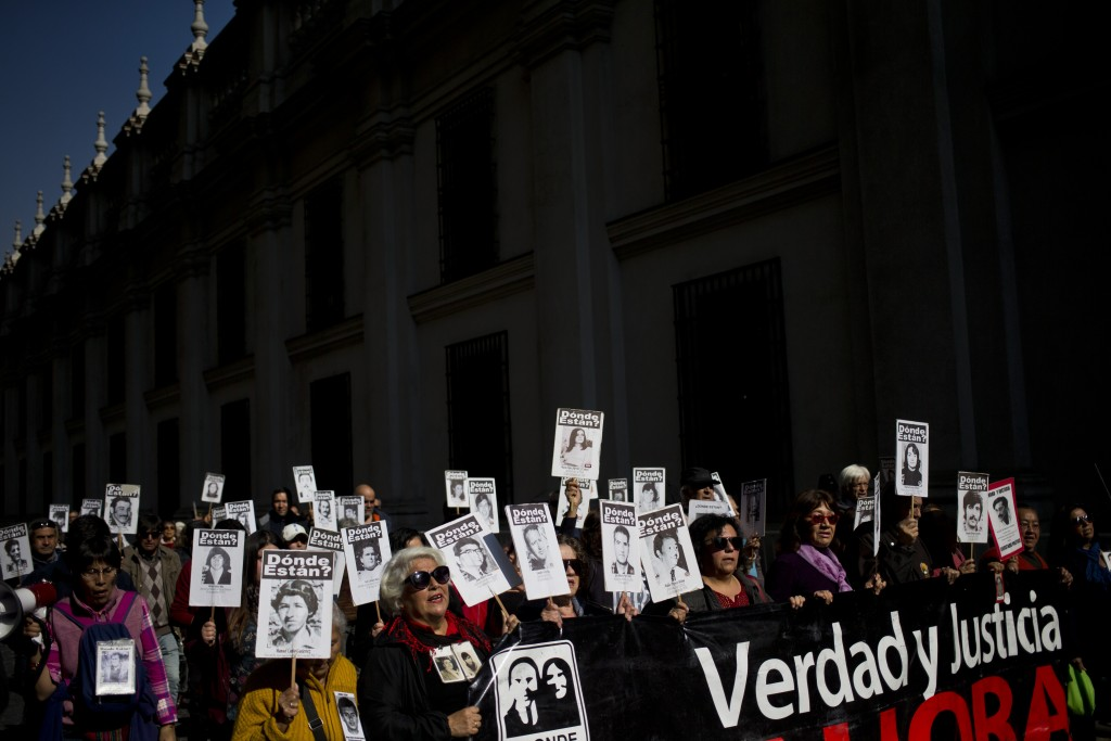 Ana Carreño, front left wearing sunglasses, marches with others past La Moneda presidential palace, carrying portraits of her father Manuel and brothe...