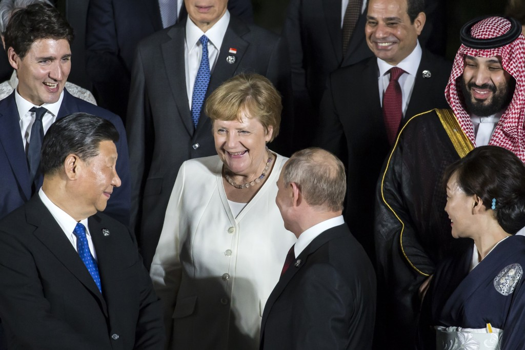 Germany's Chancellor Angela Merkel, center, speaks to China's President Xi Jinping, left, and Russia's President Vladimir Putin, second right, during ...