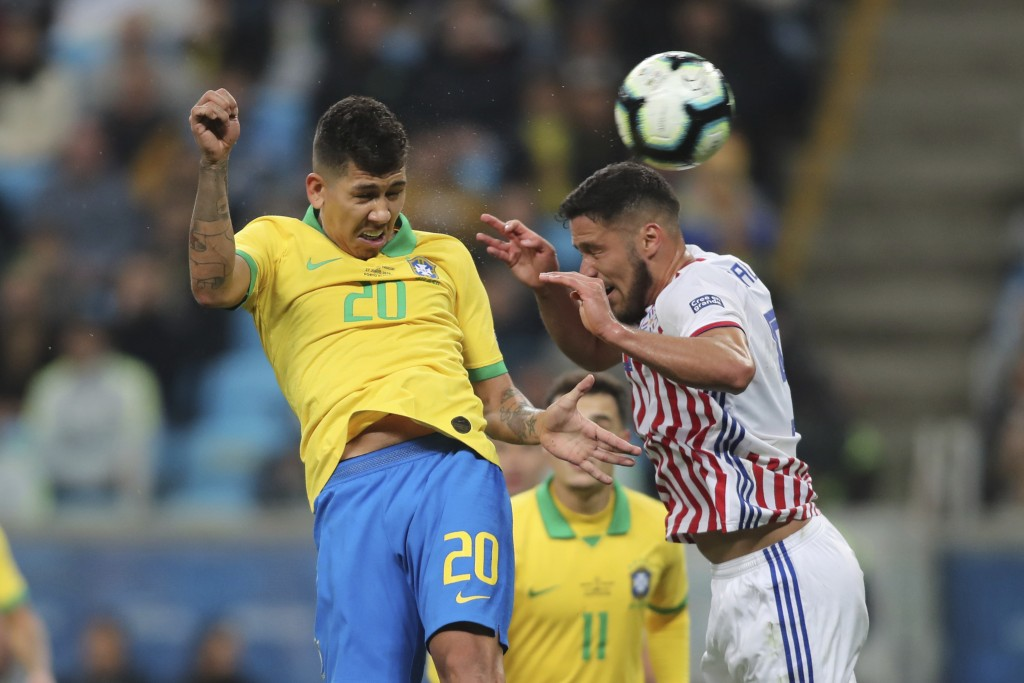 Brazil's Roberto Firmino, left heads the ball challenged by Paraguay's Bruno Valdez during a Copa America quarterfinal soccer match at the Arena do Gr...