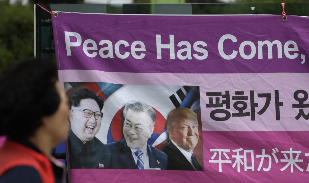 A woman walks by a banner showing images, from left, of North Korean leader Kim Jong Un, South Korean President Moon Jae-in and U.S. President Donald ...
