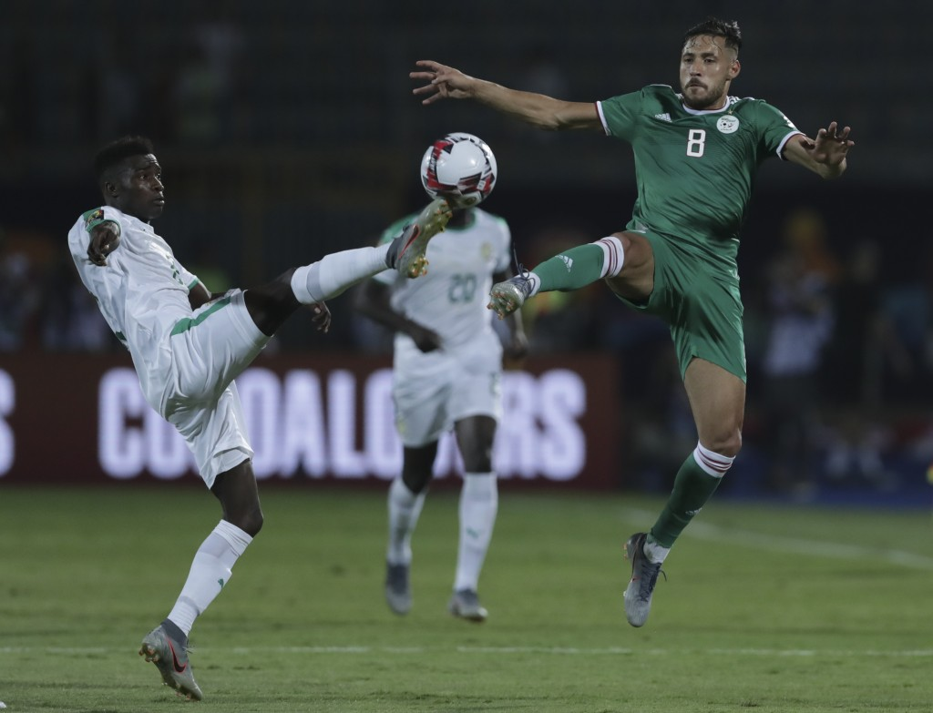 Senegal's Moussa Wague, left, and Algeria's Mohamed Belaili fight for the ball during the African Cup of Nations group C soccer match between Algeria ...