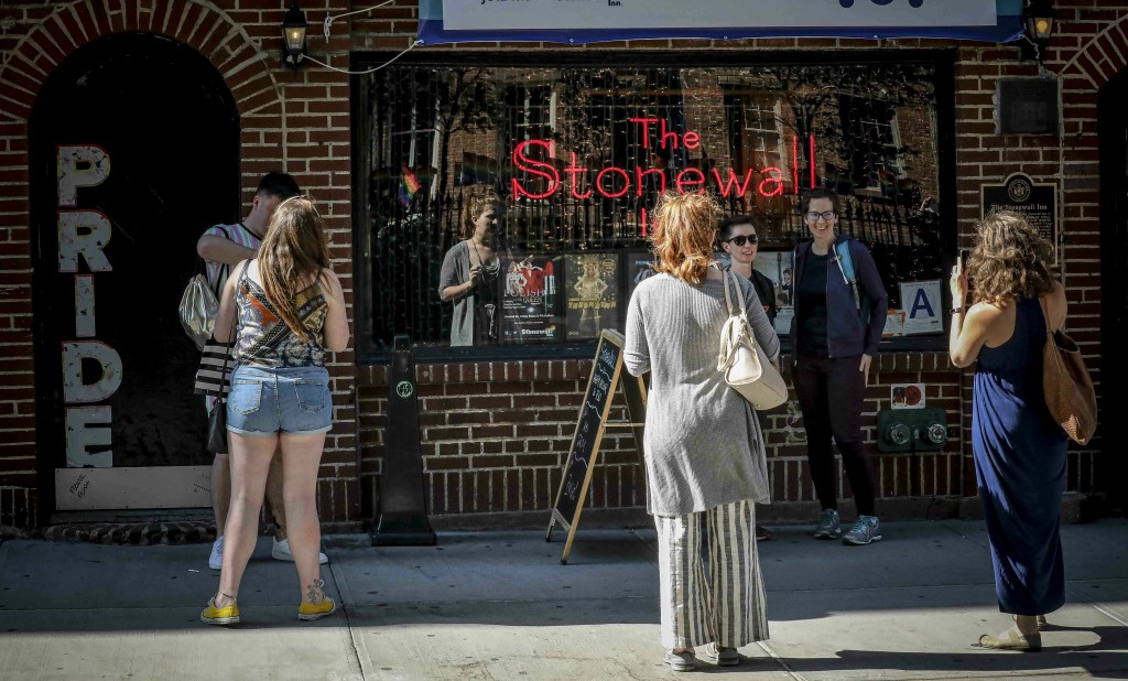 In this Monday, June 3, 2019 photo, visitors pose for photos outside the Stonewall Inn in New York. Fifty years ago, the Stonewall Inn was an undergro...