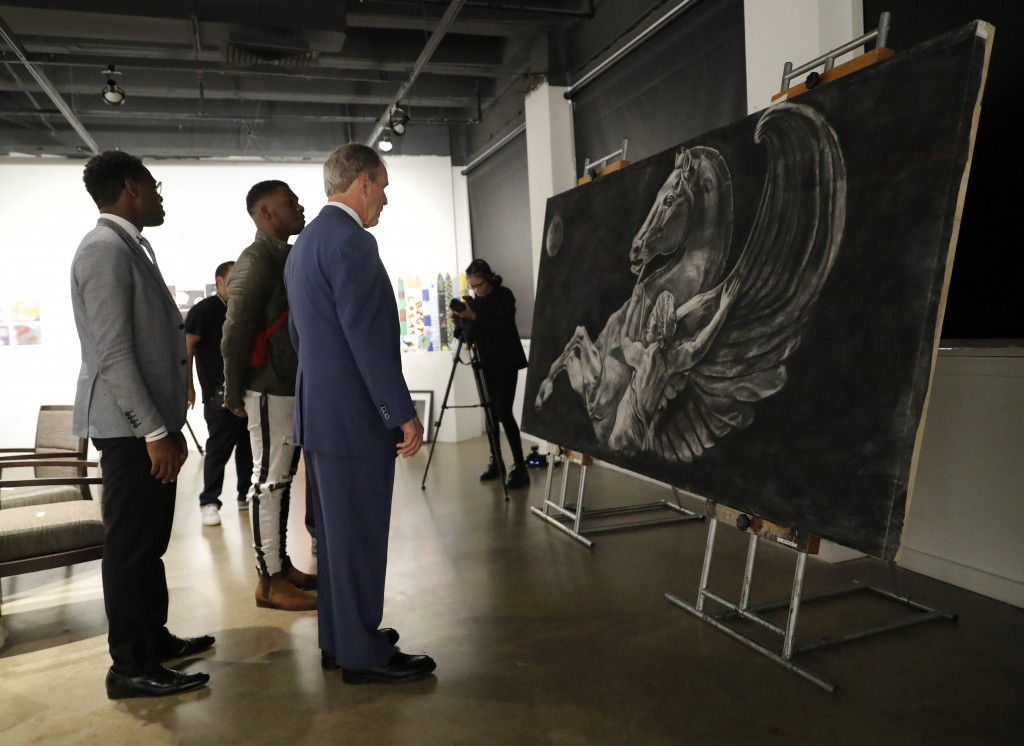 Byron Sanders, left, President and CEO of Big Thought and former President George W. Bush, right, listen as Big Thought youth participant, Isaiah, cen...