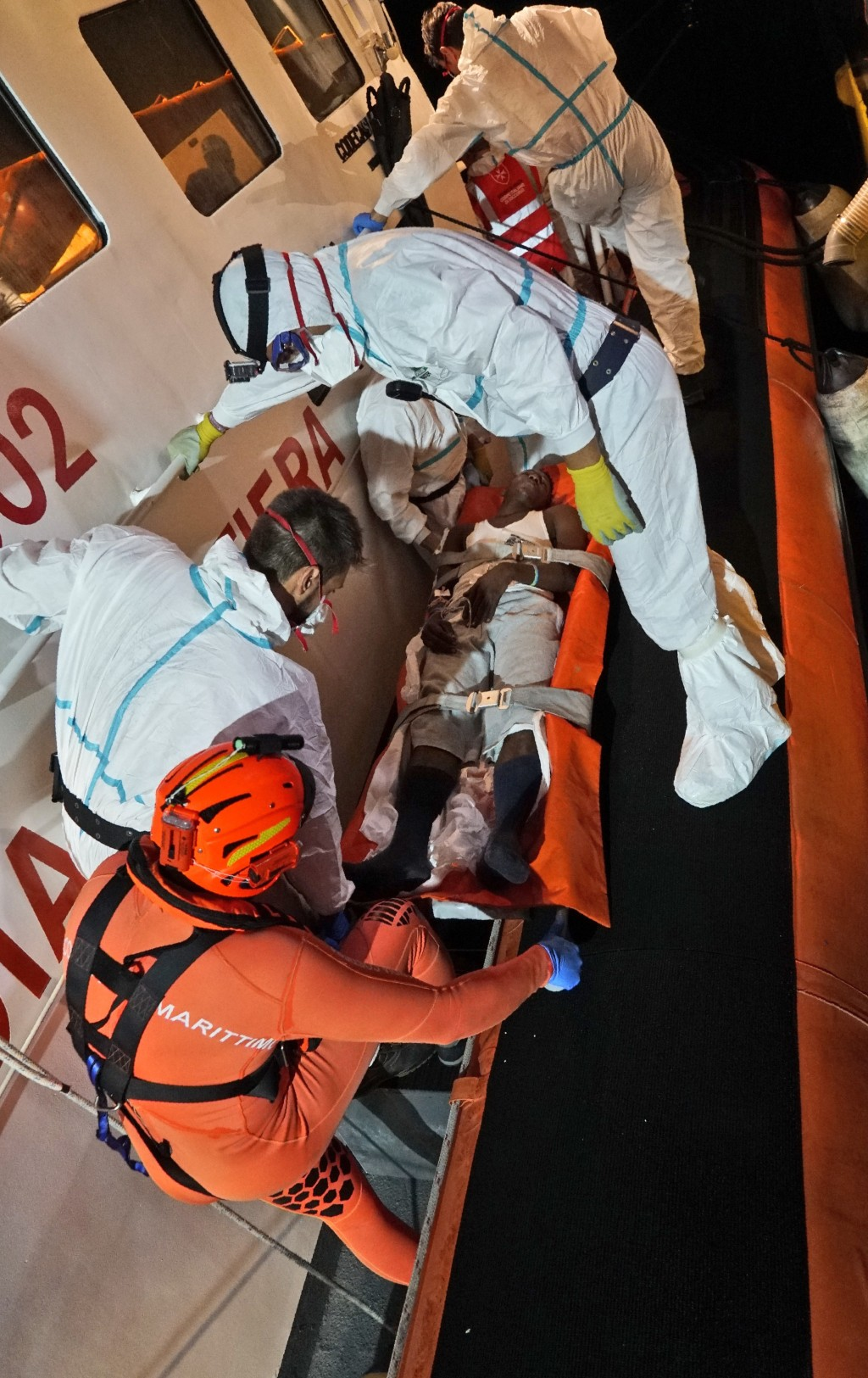 In this image taken late Thursday, June 27, 2019 and made available Friday, June 28, 2019, a migrant on a stretcher is carried onto an Italian Coast G...