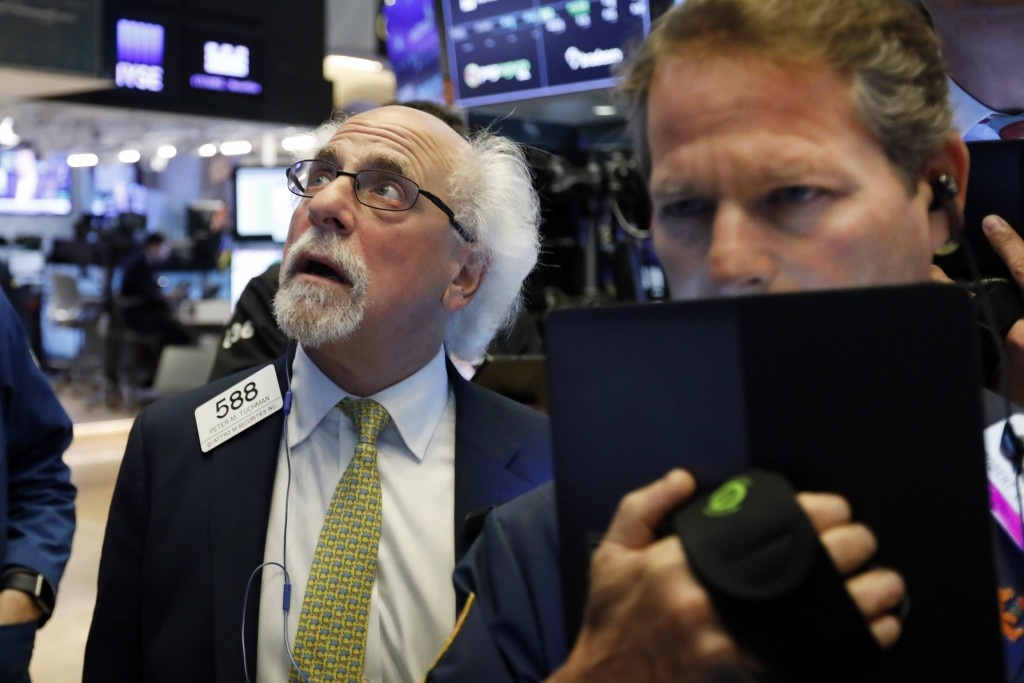 FILE - In this June 18, 2019, photo trader Peter Tuchman, left, works on the floor of the New York Stock Exchange. The U.S. stock market opens at 9:30...