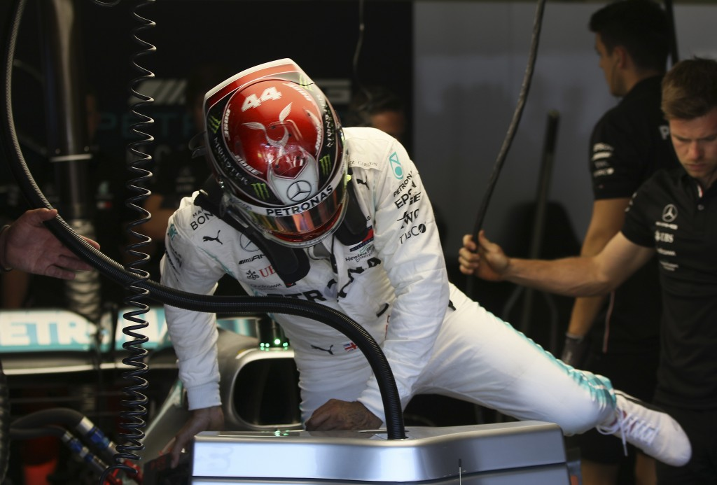 Mercedes driver Lewis Hamilton of Britain gets into his car cockpit during the first free practice session for the Austrian Formula One Grand Prix at ...