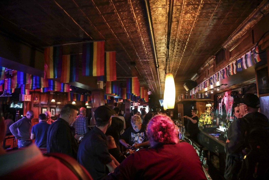 In this Monday, June 3, 2019 photo, customers gather at the Stonewall Inn in New York. The original Stonewall Inn didn't survive the 1969 police raid ...