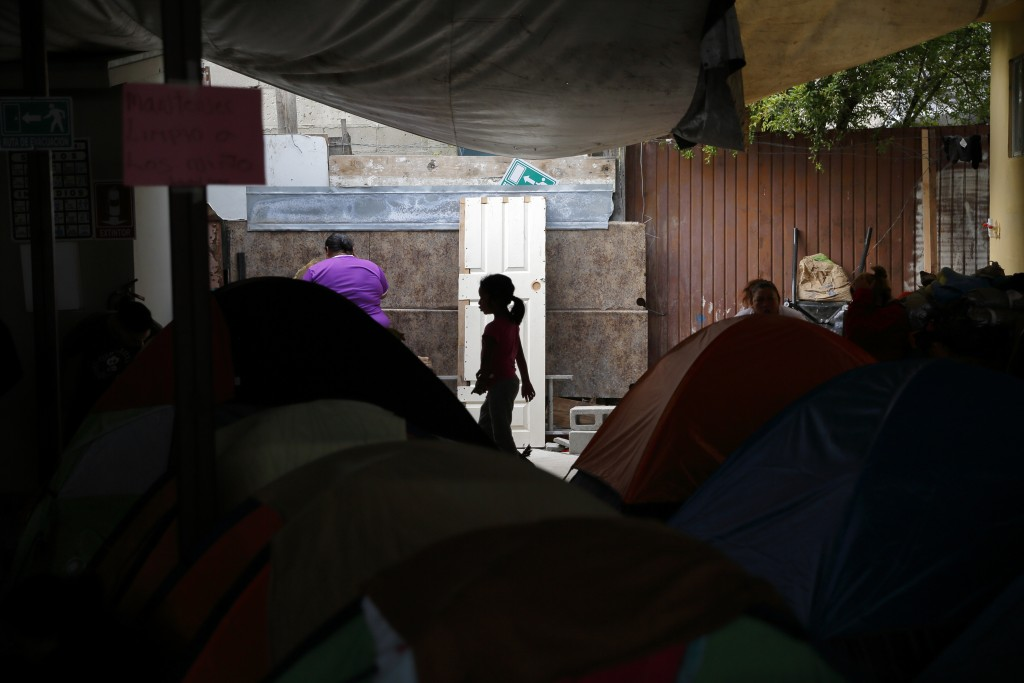FILE - In this April 12, 2019, file photo, a girl from the Mexican state of Guerrero passes rows of tents as her family waits at a shelter of mostly M...