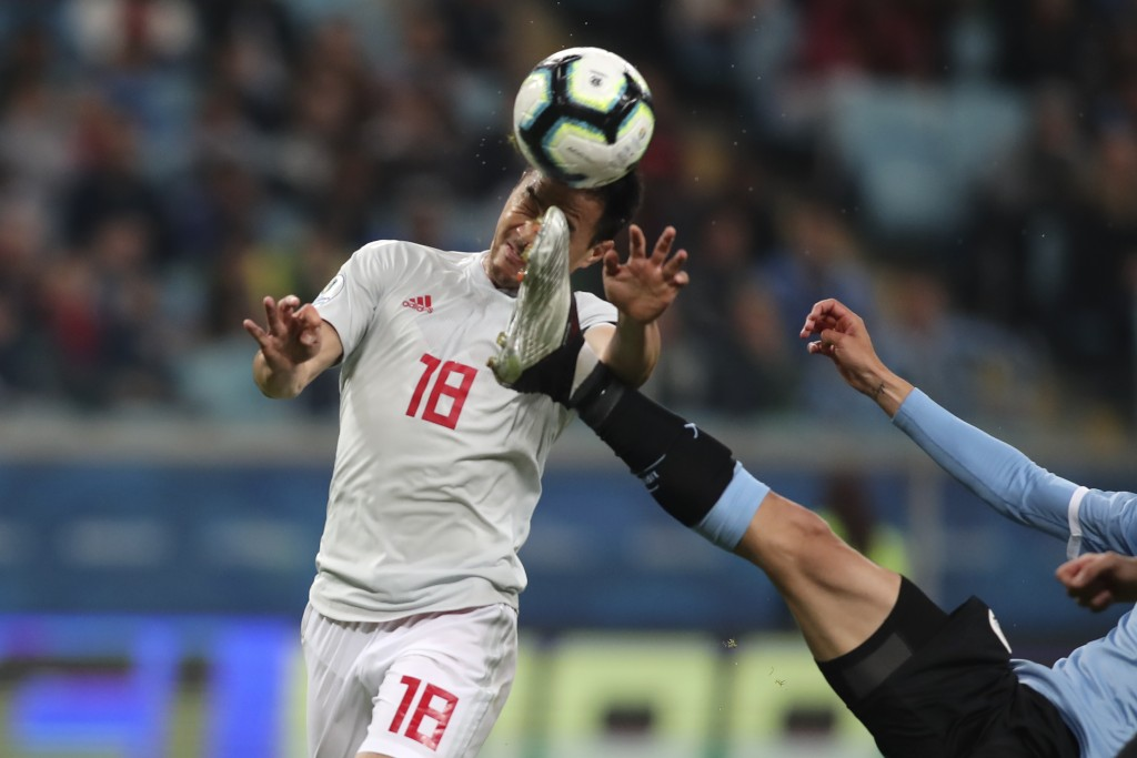 Japan's Shinji Okazaki, left, jumps for a header challenged by Uruguay's Rodrigo Bentancur, during a Copa America Group C soccer match at the Arena Gr...