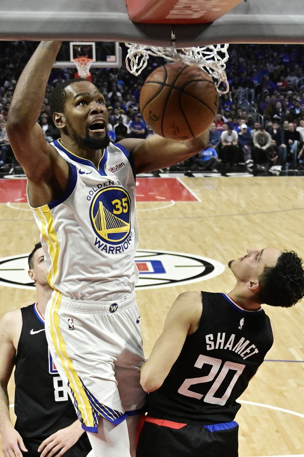 FILE - In this April 21, 2019, file photo, Golden State Warriors forward Kevin Durant, top, dunks as Los Angeles Clippers guard Landry Shamet defends ...