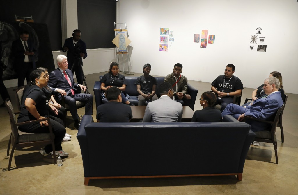Former Presidents Bill Clinton, left, and George W. Bush, right, sit at the Meadows School of the Arts with staff and participants of the non profit y...