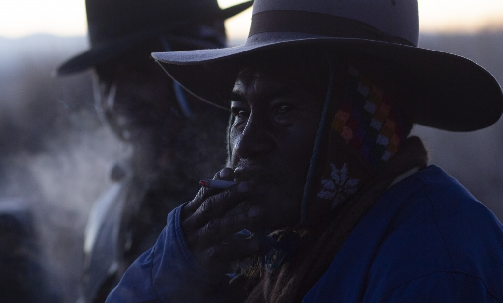 An Aymara Indian smoke a cigarette during a New Year's ritual at the Bolivian ruins Lukurmata, early Friday, June 21, 2019. Aymara communities are cel...