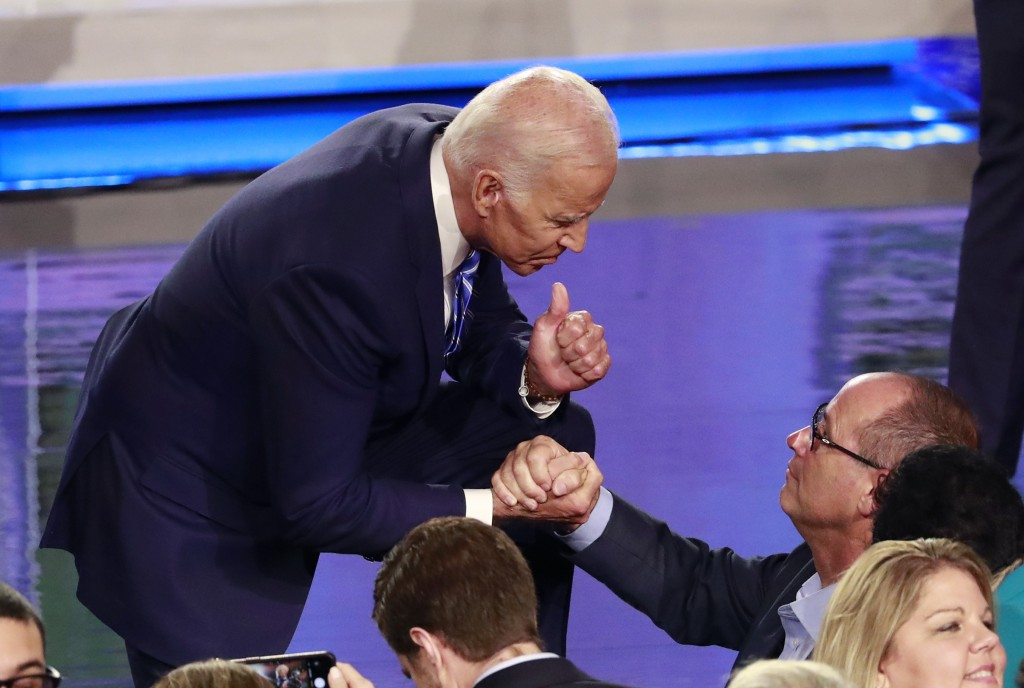 Democratic presidential candidate former vice president Joe Biden grabs the hand of Fred Guttenberg, who lost a daughter in the Parkland shooting foll...