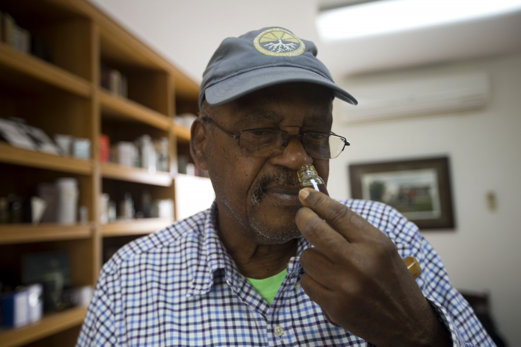 In this May 27, 2019 photo, Pierre Leger smells a perfume at the Frager's vetiver factory, in Les Cayes, Haiti. Haiti produces more than 70 tons of ve