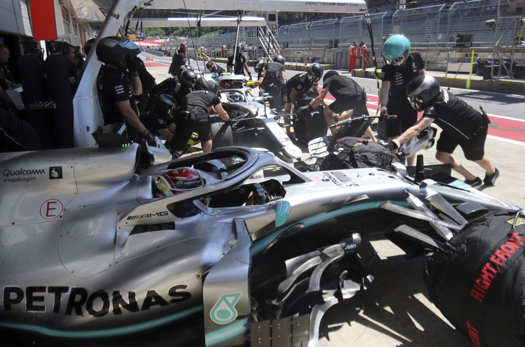 Mercedes driver Lewis Hamilton of Britain, in the foreground, sits in his car as mechanics work on the car of teammate Valtteri Bottas of Finland, in ...