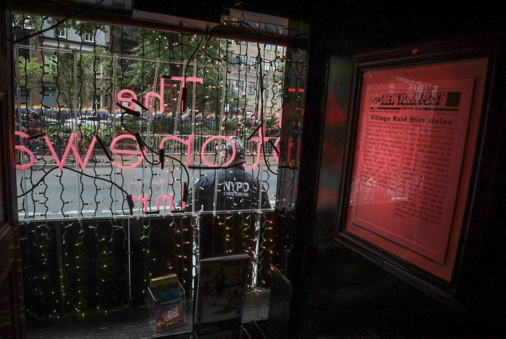 In this Friday, June 14, 2019 photo, a police officer stands outside the Stonewall Inn, where a framed news clipping highlights the 1969 riots that fo...