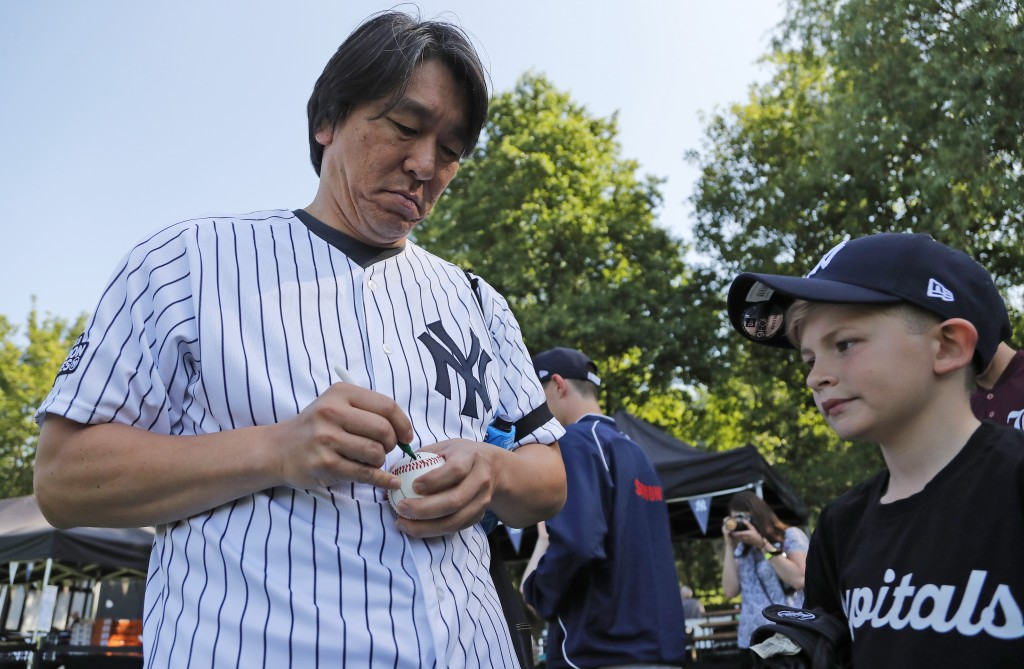 Yankees' Masahiro Tanaka signs a ball for a young fan during a private Baseball Clinic in London, Thursday, June 27, 2019. The Yankees are hosting for...