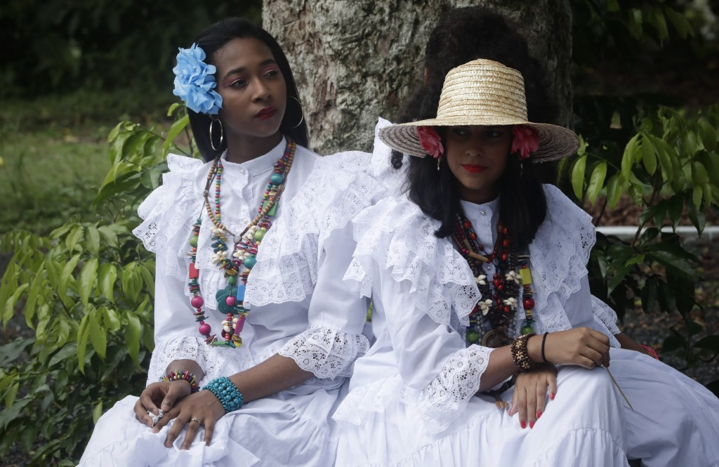 Women wearing Panamanian traditional dress rest under a tree near Fort San Lorenzo, on a promontory overlooking the mouth of the Chagres River, on Pan...